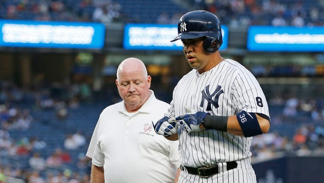 New York Yankees' Carlos Beltran, right, leaves the game with trainer Steve Donohue after an injury while running to first base on a single during the first inning of a baseball game against the Texas Rangers, in New York, Tuesday, June 28, 2016.
