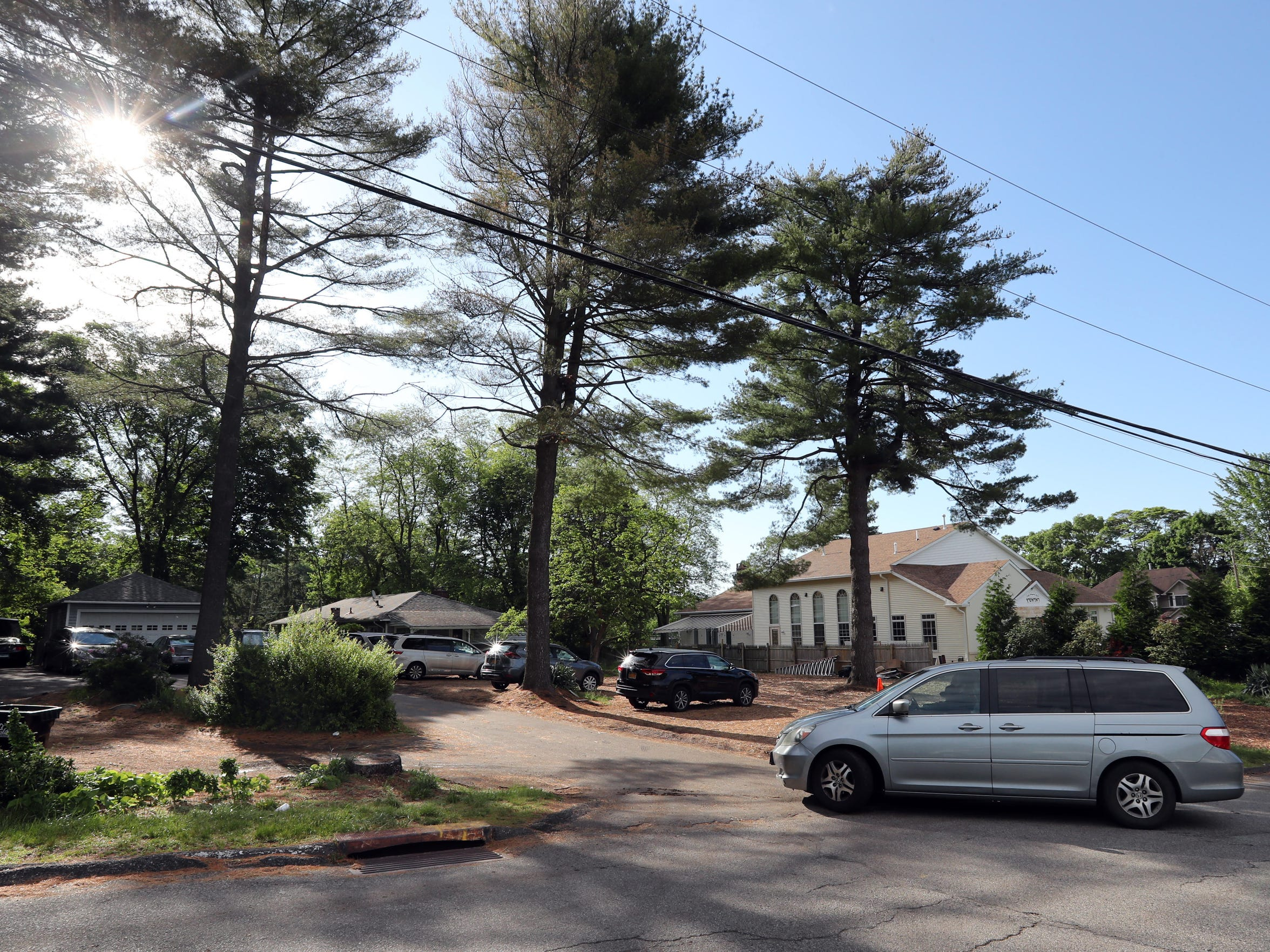 A minivan backs out of a gravel parking lot next to Bais Hamedrash Radashitz, an Orthodox synagogue on Echo Ridge Road in Airmont during the morning hours of June 5, 2018. Congregants of the synagogue park in this auxiliary lot and on the street when the parking lot at the synagogue is filled during morning worship six days a week.