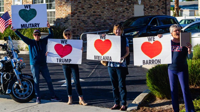 Supporters of President Donald J. Trump hold signs and hope for a glimpse of the President as the  presidential motorcade passes by Southern Boulevard on Sunday, Jan. 5, 2020.