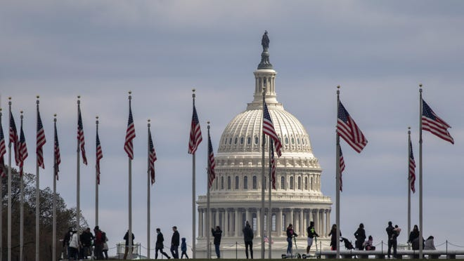 People walk among U.S. flags with the U.S. Capitol in the background, Sunday, March 15, 2020, in Washington. House Speaker Nancy Pelosi, D-Calif., said Congress has started work on a new coronavirus aid package after the one just approved by the House early Saturday.