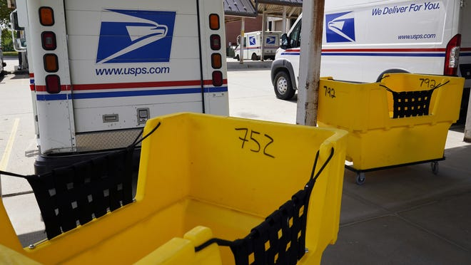 Mail delivery vehicles are parked outside a post office in Boys Town, Neb., Tuesday.