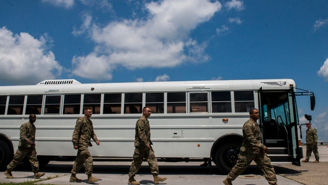 Soldiers exit the bus after arriving at Fort Campbell, following their 9-month deployment.