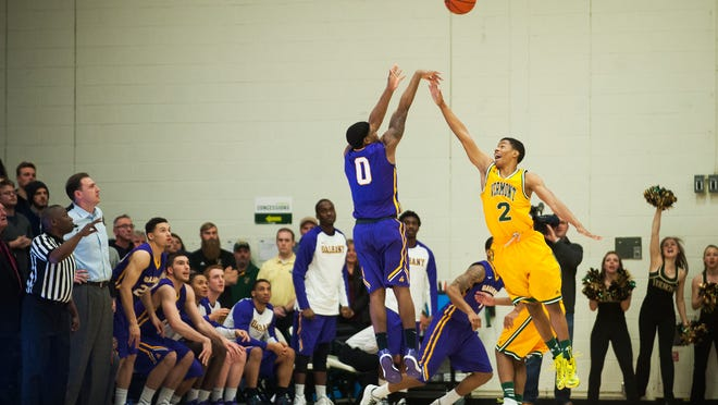 Great Danes guard Evan Singletary, left, hits a 3-point shot in the 1.5 seconds of regulation to beat Vermont during the men's basketball game between the Albany Great Danes and the Vermont Catamounts at Patrick Gym on Wednesday night.