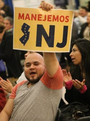"""Yony Dubon, an undocumented person from Guatemala, living in New Jersey holds up a sign that translates to """"Lets Drive NJ"""" in Elizabeth."""