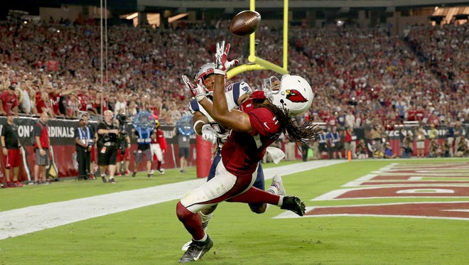 Arizona Cardinals wide receiver Larry Fitzgerald (11) catches the ball for a touchdown as New England Patriots cornerback Logan Ryan (26) defends during the fourth quarter of an NFL football game between the Arizona Cardinals and the New England Patriots in Glendale, Az., on Sunday, Sept. 11, 2016.  This was Fitzgerald's 100th career touchdown.