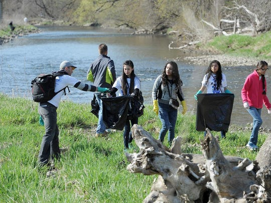 Griffin Knipp (left) picks up trash with a group of kids from the Cristo Rey Jesuit High School along the Hank Aaron State Trail and the Menomonee River near Miller Park in 2016. The cleanup was part of Work Play Earth Day events.