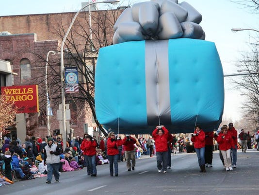 Marchers escort a helium balloon  down Cumberland Street in the Community of Lebanon Association Holiday Parade.