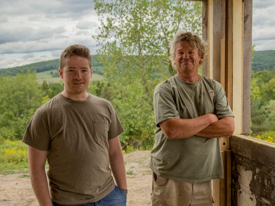 Caleb Dolph, left, and Buzz Dolph, owner of Tiny Timbers LLC, stand in the unfinished interior of a tiny house prototype on their property on Quarry Road. Buzz sees his idea, a modular tiny house, as a potentially $10 million if he can sell 200 each year.