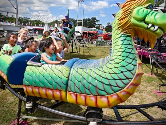 """Children react to the tight turns of the """"Dragon Wagon"""" Ride during the last day of the 2016 Benton County Fair in Sauk Rapids."""