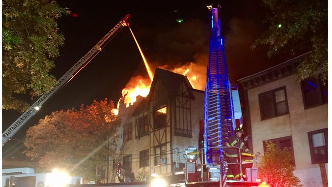 Firefighters battle flames to Palmer Avenue apartment house in Larchmont from ladder trucks