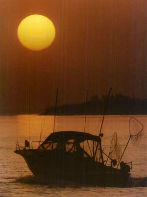 Anglers head out onto Lake Ontario at sunrise.