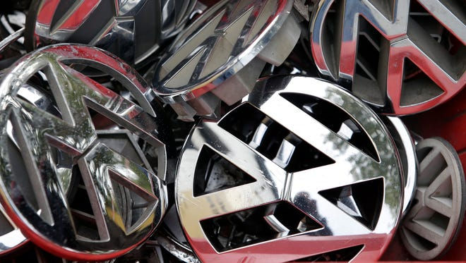 Company logos of the German car manufacturer Volkswagen sit in a box at a scrap yard in Berlin, Germany.