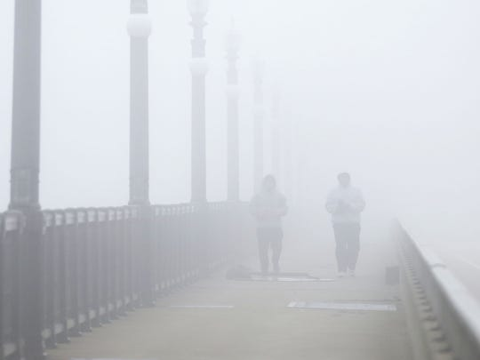 """Marat McMaster, 19, left, and Dewayne Brown, 57, both of Detroit,  take a morning stroll across the MacArthur Bridge from Belle Isle on Monday, Dec. 7, 2015. The two did not start off walking together. It is due to the fog that they ended up walking and talking. The younger walker, McMAster, realized he took a wrong turn and could not find his way to the bridge. He says luckily, """"I ran into him and met Dewayne and he showed me the way."""""""