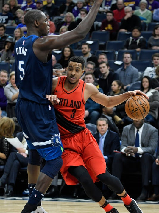 Portland Trail Blazers' C.J. McCollum, right, attempts to drive around the Minnesota Timberwolves' Gorgul Dieng, left, in the half of an NBA basketball game Sunday, Jan. 14, 2018, in Minneapolis. (AP Photo/Tom Olmscheid)