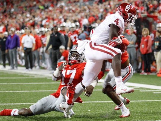 Oklahoma running back Trey Sermon, right, scores a touchdown past Ohio State linebacker Jerome Baker, left, and cornerback Damon Arnette during the second half of an NCAA college football game Saturday, Sept. 9, 2017, in Columbus, Ohio. Oklahoma defeated Ohio State 31-16. (AP Photo/Paul Vernon)