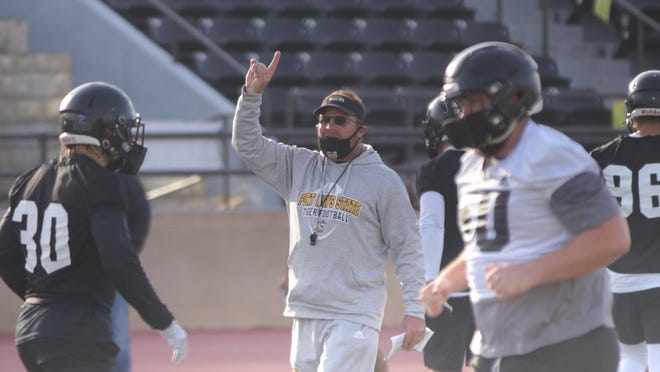 Fort Hays State football coach Chris Brown instructs his team during its first fall practice on Tuesday at Lewis Field Stadium.