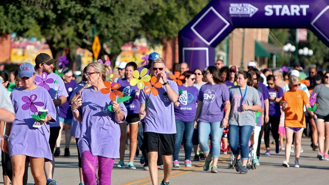 Hundreds of people walk down Ohio Avenue carrying pinwheel flowers near the start of the 2017 Walk to End Alzheimer's Saturday morning in Wichita Falls.