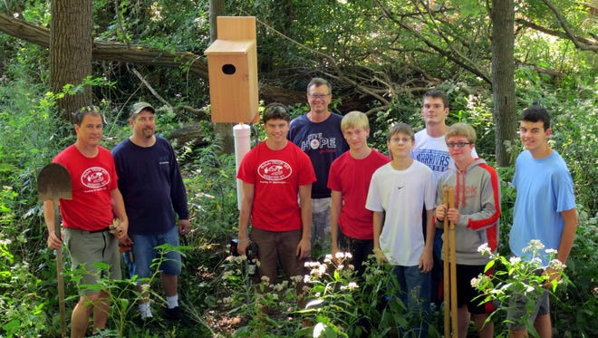 Matthew Streit, third from left, stands with family members and volunteers next to one of the birdhouses they installed on the trail.