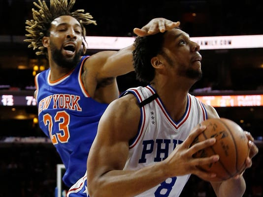 Philadelphia 76ers' Jahlil Okafor, right, tries to shoot as New York Knicks' Derrick Williams defends during the second half of an NBA basketball game, Friday, Dec. 18, 2015, in Philadelphia. New York won 107-97. (AP Photo/Matt Slocum)