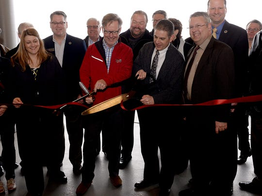 Tom Dickson, owner of the Lansing Lugnuts, center left, and Lansing Mayor Virg Bernero, ceremoniously cut the ribbon for the renovations at the Cooley Law School Stadium Thursday, April 8, 2015.