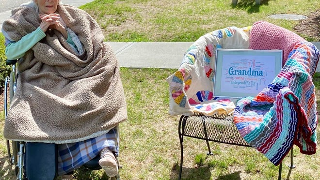 Irene Burke of Marshfield, who turns 100 on Aug. 31, 2020, sits outside Bay Path nursing home in Duxbury on Sunday with several of the blankets and afghams she has made over the years for her family.   Photo/Cheryle Gallagher