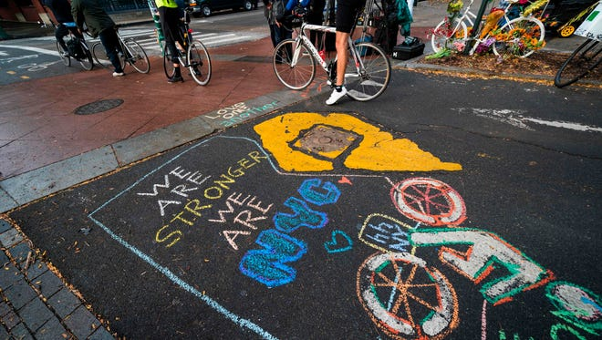 Cyclists ride past a message paying tribute to the Oct. 31 terror attack victims.