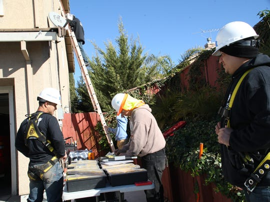 GRID Alternatives and Rancho Cielo Construction Academy students work on a installing solar panels at a Soledad home.