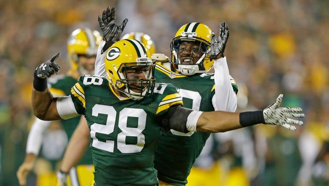 Packers cornerback Sean Richardson (28) celebrates a defensive play with cornerback Demetri Goodson (39) against the Seattle Seahawks at Lambeau FIeld
