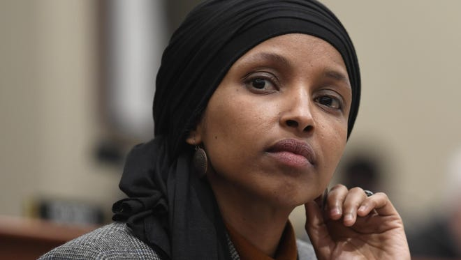 In this March 12, 2019, photo, Rep. Ilhan Omar, D-Minn., listens as Office of Management and Budget Acting Director Russ Vought testifies before the House Budget Committee on Capitol Hill in Washington.