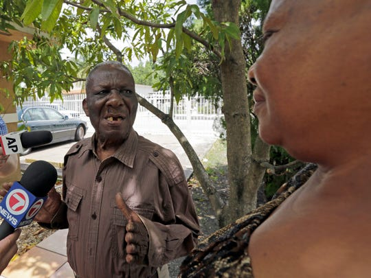 Gabriel Jean, left, and his daughter, Rosemary LeBranch, right, talk to reporters at their home in the Wynwood area of Miami, Monday, Aug. 1, 2016. LeBranch told reporters that she was informed by a phone call by a health official the her father was infected with the Zika virus.
