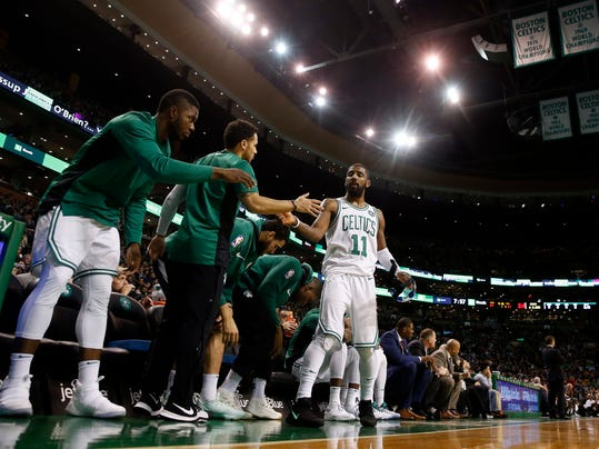Boston Celtics' Kyrie Irving gets congratulated at the bench during the first quarter of their 111-100 win over the Milwaukee Bucks in an NBA basketball game in Boston, Monday, Dec. 4, 2017. (AP Photo/Winslow Townson)