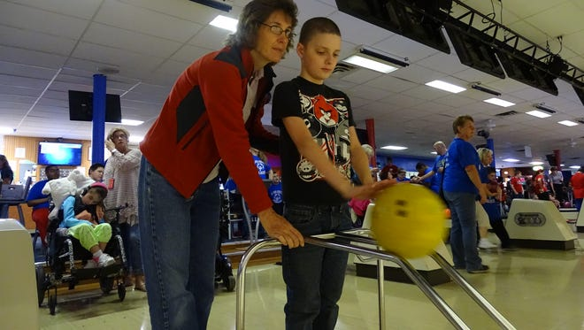 Debbie Kennedy guides one of her students, Eian Davison, as he takes his turn bowling at Friday's Special Olympics Ohio bowling event. The local AMVETS chapter sponsored the event at Shawnee Lanes for over 100 Special Olympics athletes.