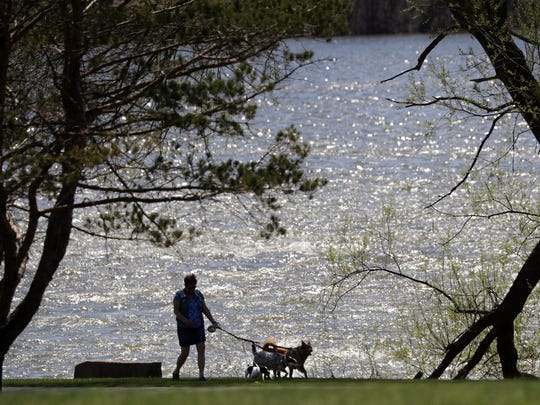 Louiose Becklund, Kaukauna, walks her dogs Monday on a trail along the Fox River at Island Park.