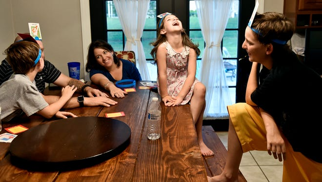 """Callyn Lee, 6, center, laughs as brother Aidan, 11, tries to guess his """"Hedbanz"""" card during the Lees' """"family fun night"""" at their York Township home. Heather and Robert Lee dedicate every Friday evening to family-friendly activities like board games or a movie to get electronics-free face time with their three children."""