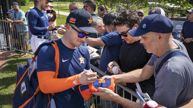 Houston Astros players Alex Bregman and Carlos Correa, background, sign autographs for fans Wednesday at FITTEAM ballpark in West Palm Beach.