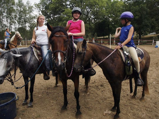 Horses and their riders take a water break during the Natural Valley Ranch kids camp in Brownsburg, Ind.