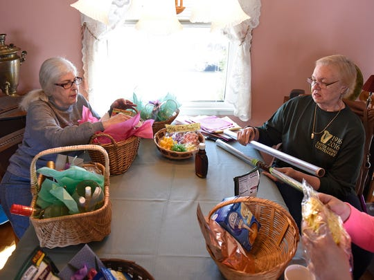 """Mary White-Levilain, left, and Jerilyn Petersen assemble baskets for the upcoming Central Minnesota Women Shine """"Spring Into Windows"""" fundraiser March 31 at the Red Carpet Martini Lounge in St. Cloud."""