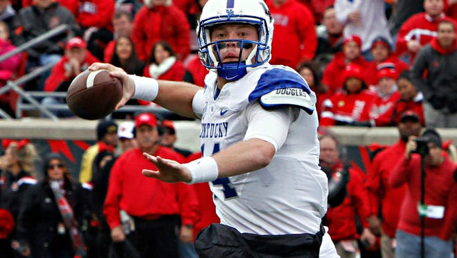 FILE - In this Nov. 29, 2014, file photo, Kentucky quarterback Patrick Towles looks to pass against rival Louisville in their NCAA college football game in Louisville, Ky. Coach Mark Stoops has named junior incumbent Patrick Towles as his starting quarterback ahead of Drew Barker. (AP Photo/Garry Jones, File)