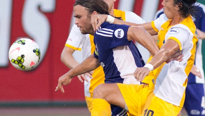 Pittsburgh (Pa.) Riverhounds defender Willie Hunt holds onto Louisville City FC forward Matt Fondy to interrupt Fondy's passing.29 Aug 2015