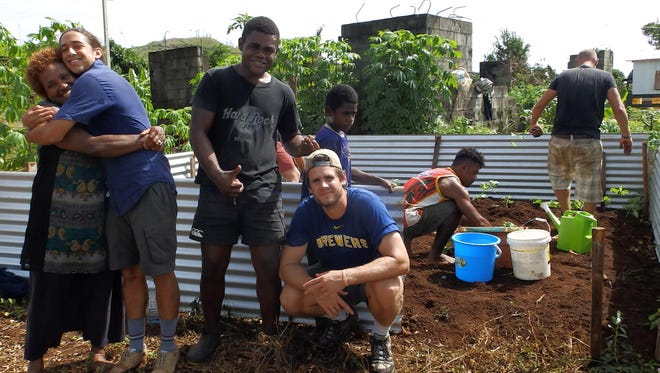 Josh Hopfensperger, center, squats in front of a vegetable garden that was planted by volunteers and villagers in Silana, Fiji.