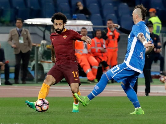 Roma's Mohamed Salah kicks the ball past Empoli's Marcel Buchel during a Serie A soccer match between Roma and Empoli, at the Rome Olympic stadium, Saturday, April 1, 2017. (AP Photo/Alessandra Tarantino)