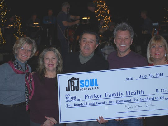 Left to right, Dr. Gail Reilly, medical director of the Parker Family Health Center; Mary Nicosia, Parker Center clinic director, Dr. Gene Cheslock, Parker Center president, Jon Bon Jovi, and Gina Petillo, Parker Center board trustee. at the Count Basie Theatre in Red Bank on Monday, Dec. 22 as Bon Jovi presents a check to the Parker Center.