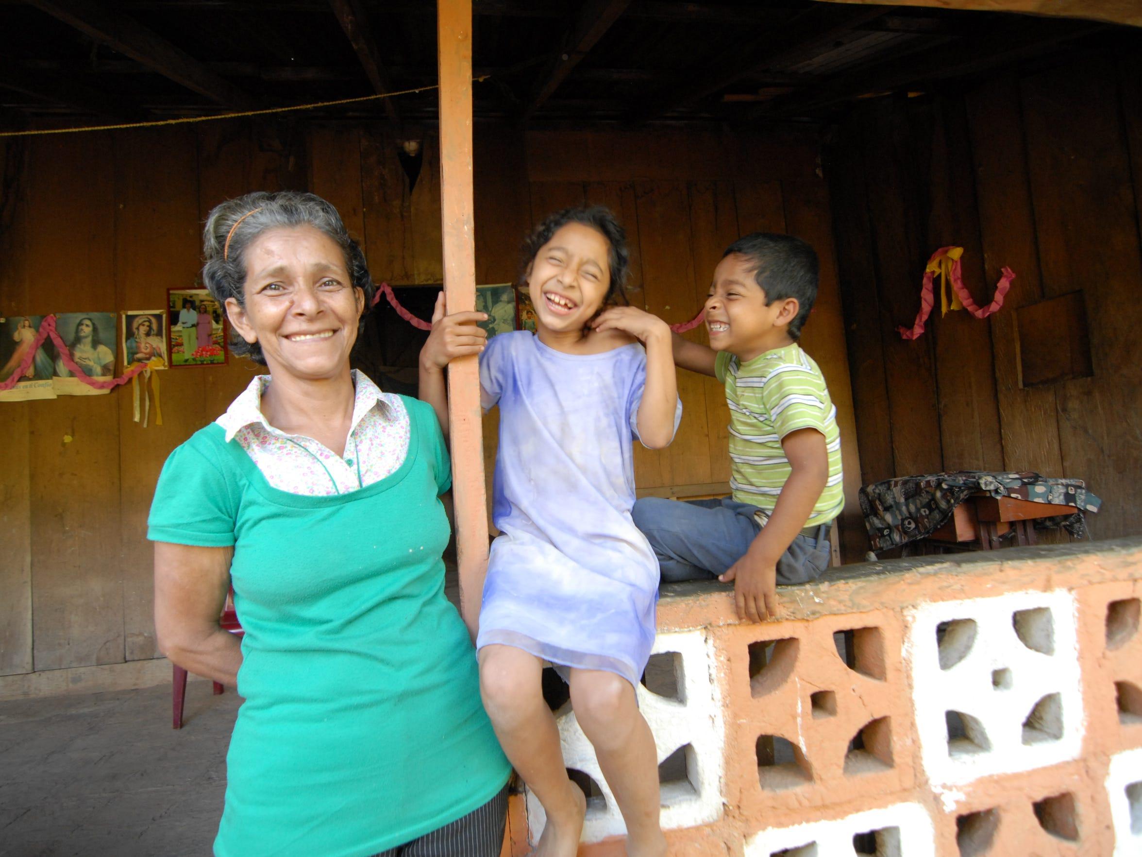 Anunciacion and her grandchildren, Alfoncina and Fernando, outside their home.