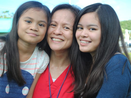 Mother Rizel Fernandez with her daughters Veronica, 10, and Joan, 15. Joan Fernandez was the first baby born at Sagua Mañagu 15 years ago July 20.