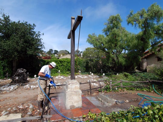 A worker washes brown paint from the memorial to Ramon