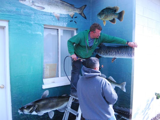 Matt McNutt, with torch, and James Smith of Serious Graphics and Signs in Yale, apply a building wrap Friday to the  River Rats clubhouse in Port Huron.