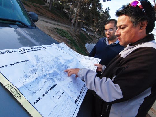 Luis Ortega, right, construction superintendent for CHISPA, and Joel Hernandez of CCA, the Center for Community Advocacy, check the plans on Tuesday morning for the long-awaited Acosta Plaza Recreation Area project.