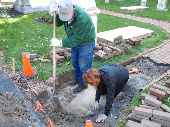 Workers dig around a recently discovered gravestone