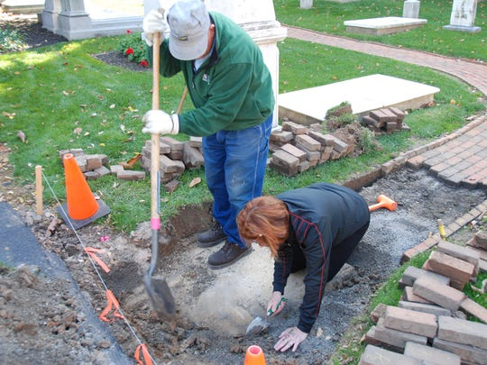 Workers dig around a recently discovered gravestone at the First Presbyterian Church of York.