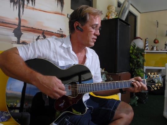 William Dillon plays guitar on the porch of his family's home in Satellite Beach in 2009